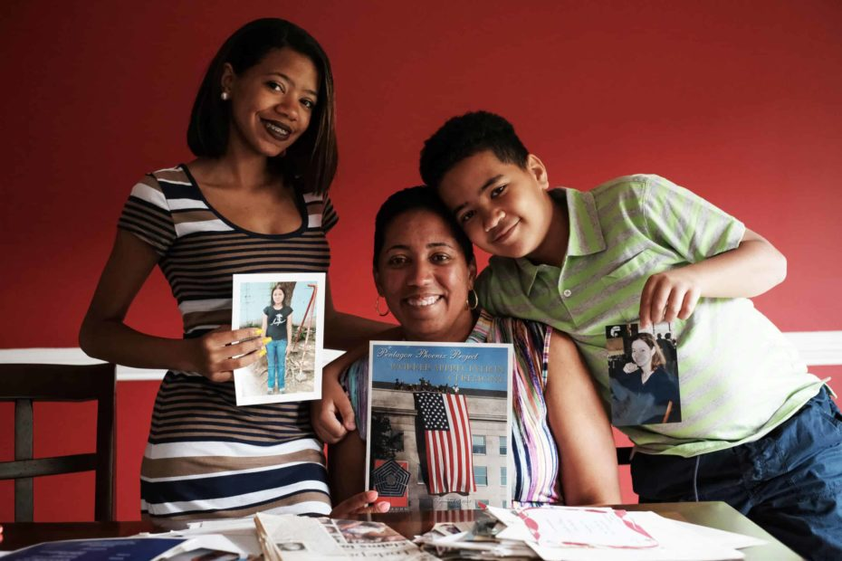 A woman and children hold up photos and smile.