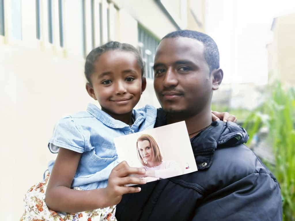 Sintayehu is holding his daughter Lisa, who is holding a photo of her father's former sponsor