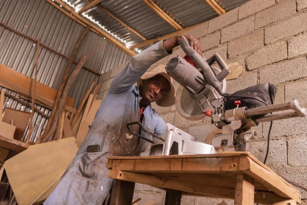 Sintayehu uses a saw in his carpentry shop. He is wearing a long blue coat and a hat.