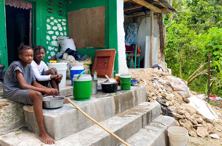 Two girls sit on concrete stairs near rubble of a home that is partially collapsed. They are preparing a fish to eat.