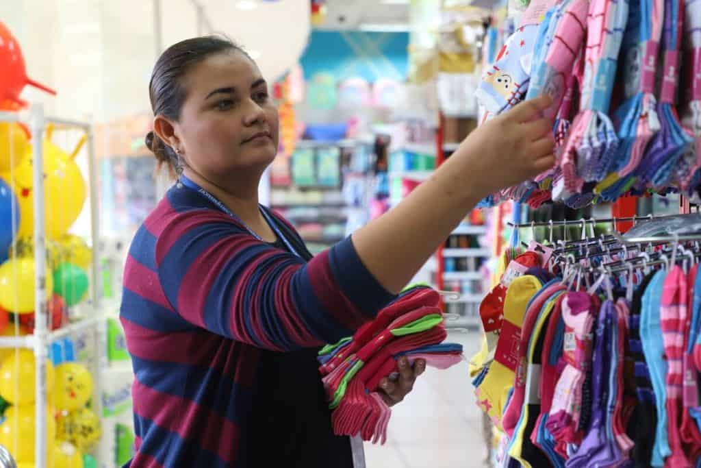 A woman wearing a maroon and blue cardigan is shopping for baby clothes at a store in El Salvador.