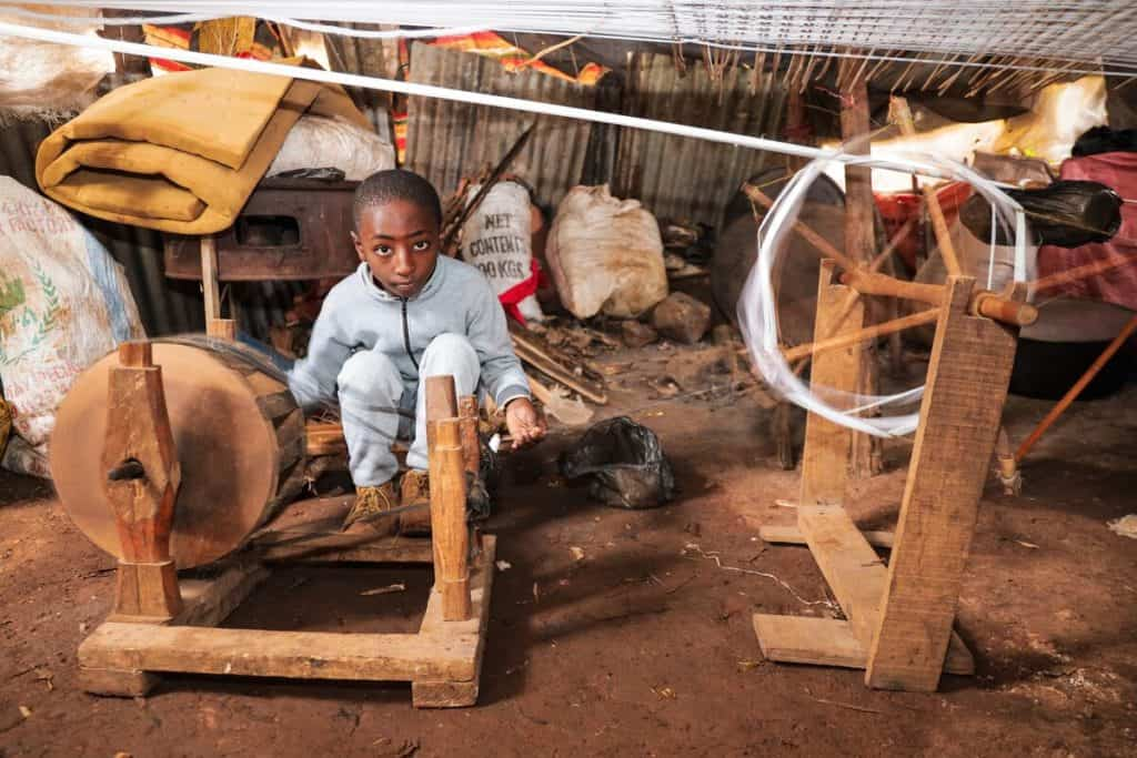 A boy wearing boots and a light colored outfit sits near a cotton wheel in Ethiopia. He is helping his father make fabric to sell at a market.