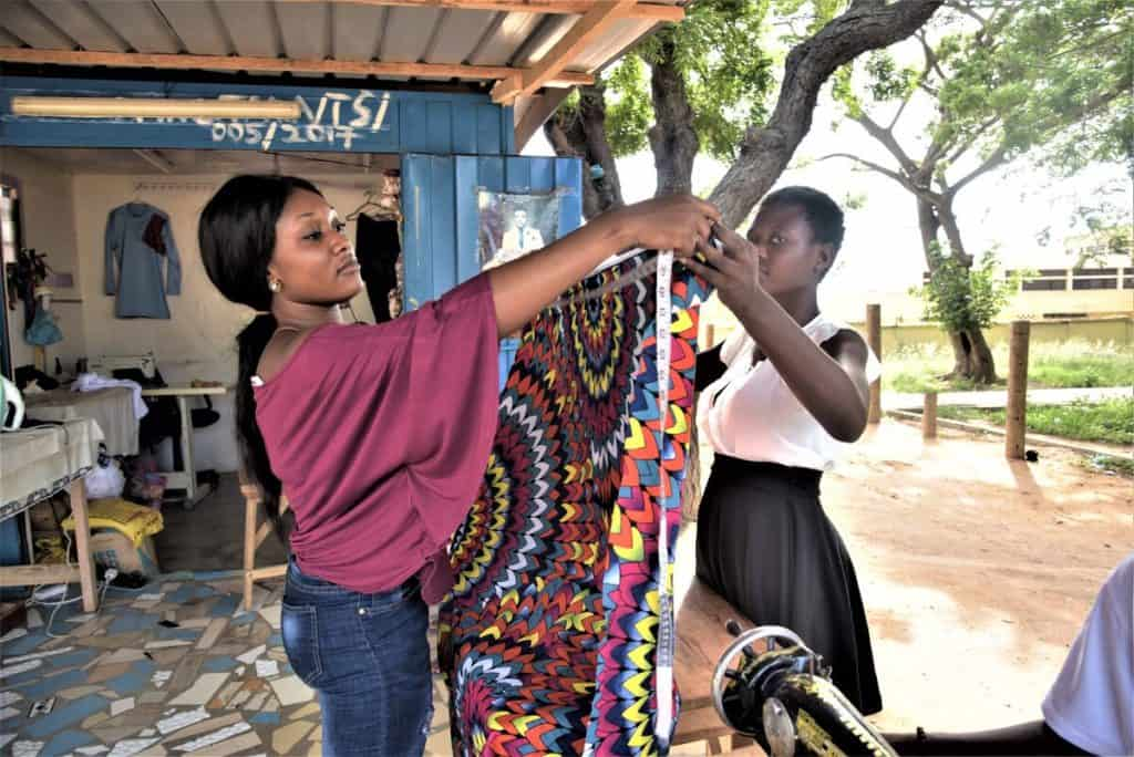 Two women in Ghana hold opposite sides of a colorful piece of fabric. One is holding a measuring tape to the fabric. She is wearing a pink shirt and blue jeans.
