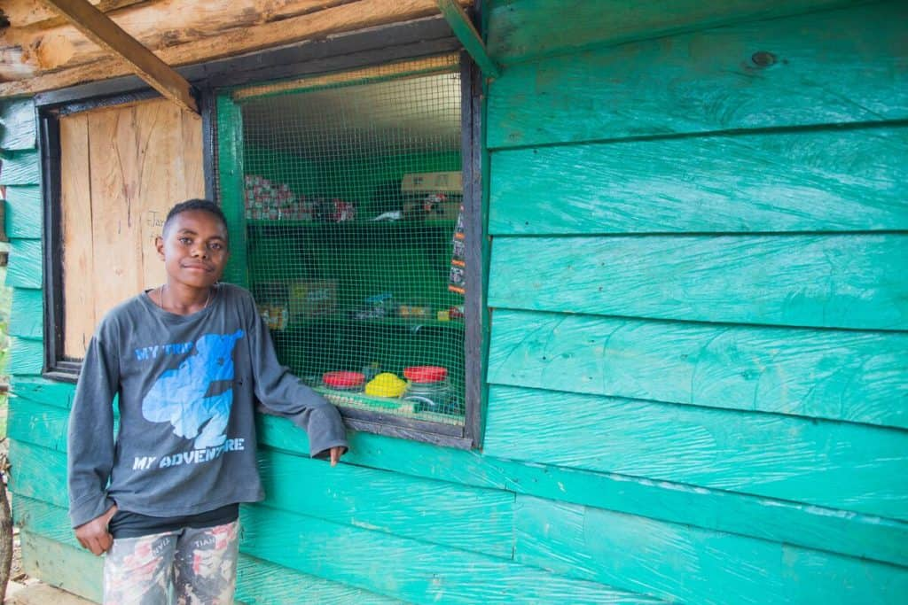 A teenage boy stands outside a shop window in Indonesia. The shop is painted teal green.