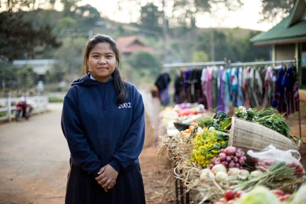 A teenage girl stands with her hands folded in front of a produce stand. In the background, a clothing stand is seen at the outdoor marketplace.