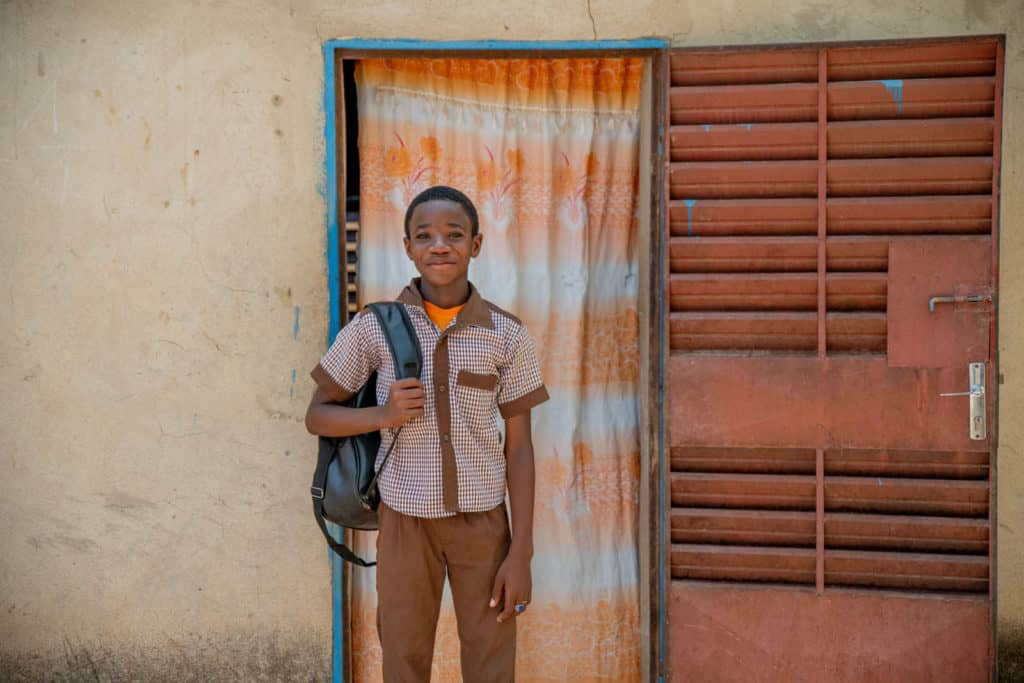 Sansan is wearing a brown and white shirt with tan pants. He is standing outside his home and is holding his back pack. Behind him there is an orange and white curtain on his door.