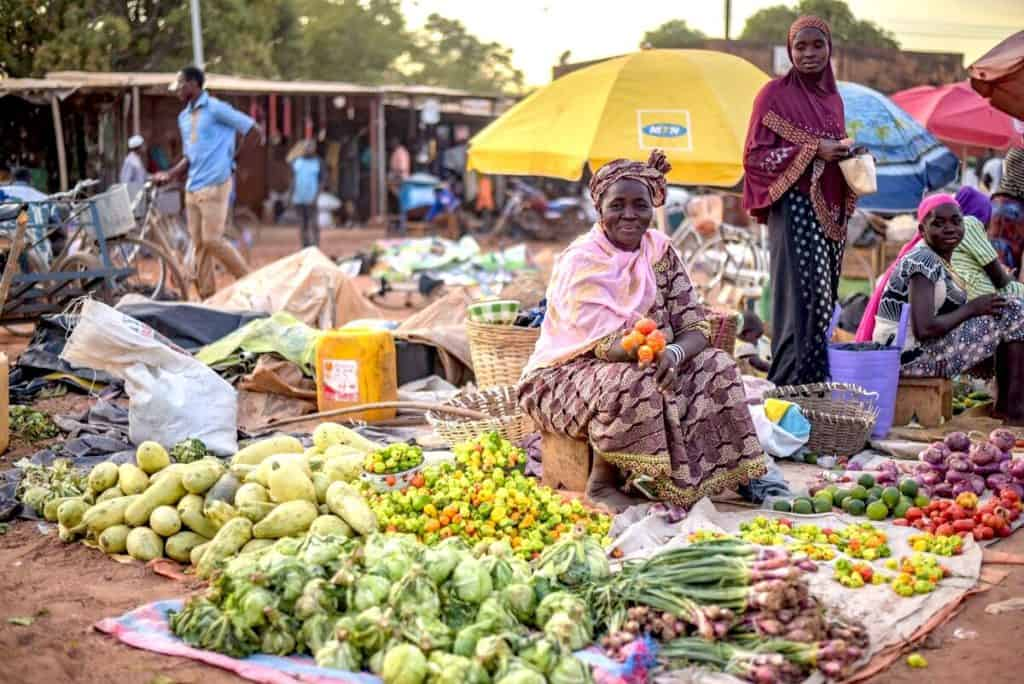 A smiling woman sits near blankets on the ground, which are covered with produce for sale. The open-air market in Burkina Faso is busy with people shopping and selling.