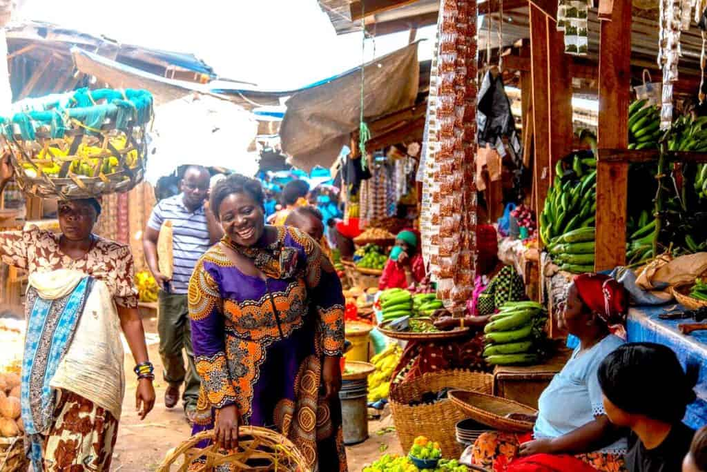 I busy outdoor marketplace in Tanzania. A smiling woman is wearing a colorful purple and orange dress. Vegetable stands selling plantains and other produce are seen behind her. A woman walks by carrying a basket of fruit on her head.