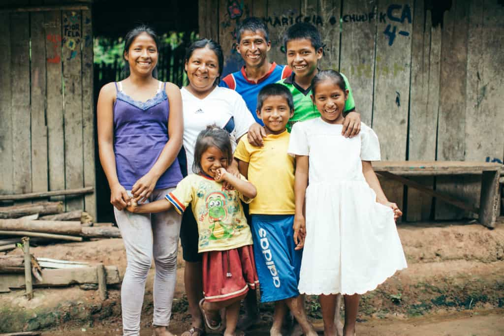 A smiling family, mother, father and children stand outside posing for a picture with their arms around each other. They wear purple, blue, white, green and yellow shirts and one girl wears a white dress. They are in front of a home made of wood boards and a thatched roof.