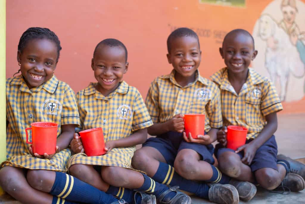 Four children in uniforms sitting on the ground. They are all holding red cups.