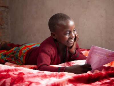 Promise is wearing a maroon shirt with a red and blue patterned skirt. She is laying on her bed and is reading a letter from her sponsor.