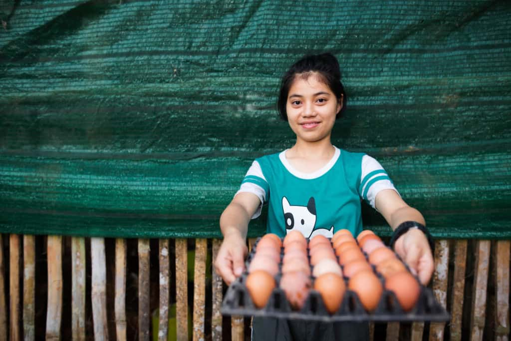 Rungnapa is showing an egg tray after she collected eggs at the agriculture project site. She is wearing a green tee shirt and is standing in front of a green tarp. Rungnapa is smiling at the camera.