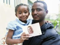 A father holds his daughter, who is holding a photo of a woman