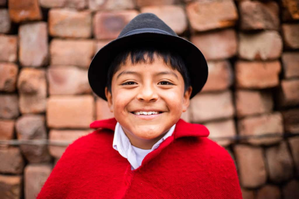 Jostin is wearing traditional clothing, a black hat and a red cape. He is standing in front of a brick wall.