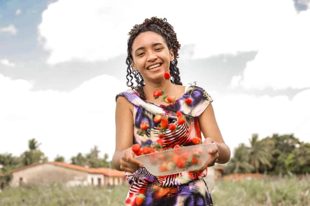 Grazielle is wearing a purple patterned dress. She is is standing outside with a plastic bowl full of strawberries that she is tossing up into the air.