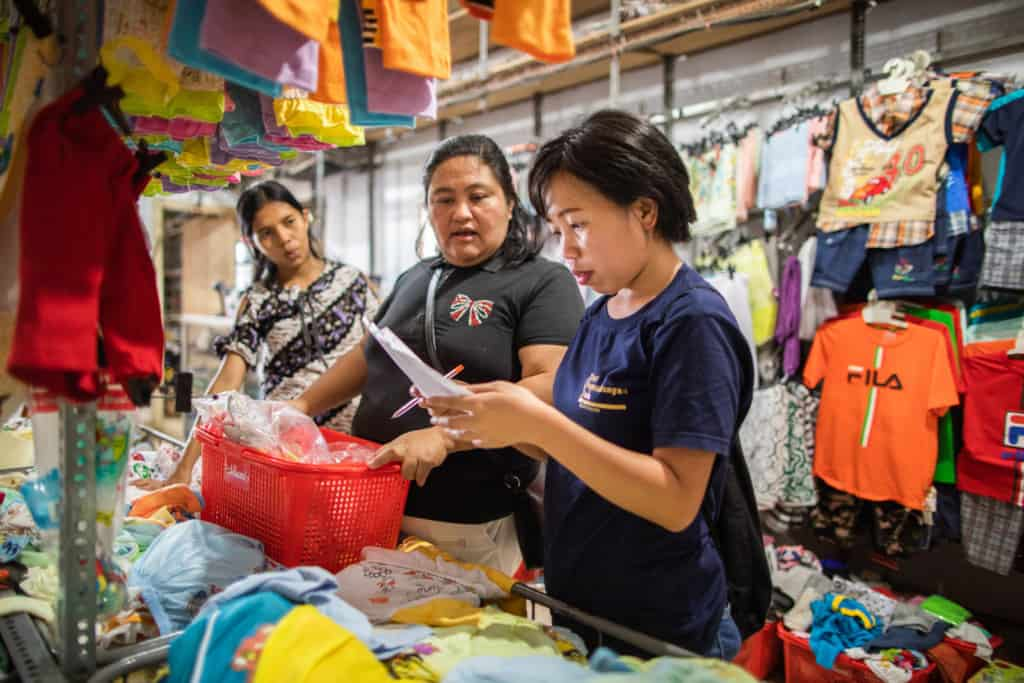 Injilia Mundung (right) is checking a shopping list to make sure 15 Survival beneficiaries get appropriate Christmas gifts. Injilia and Donna Mangindaan (middle) are shopping at one of the clothes shops in Manado city.