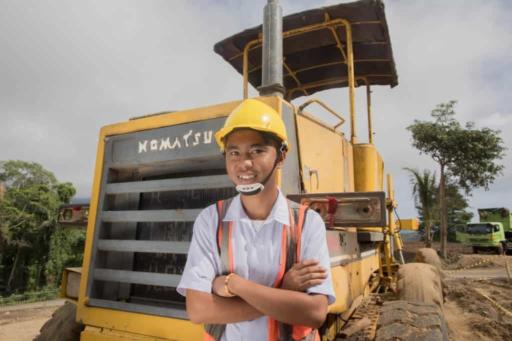 Buyung is wearing a white shirt, orange vest, and yellow hard hat. He is standing with his arms crossed in front of him. He is standing in front of a large yellow grader that is parked on the side of the road. He dreams of operating machines as a career.