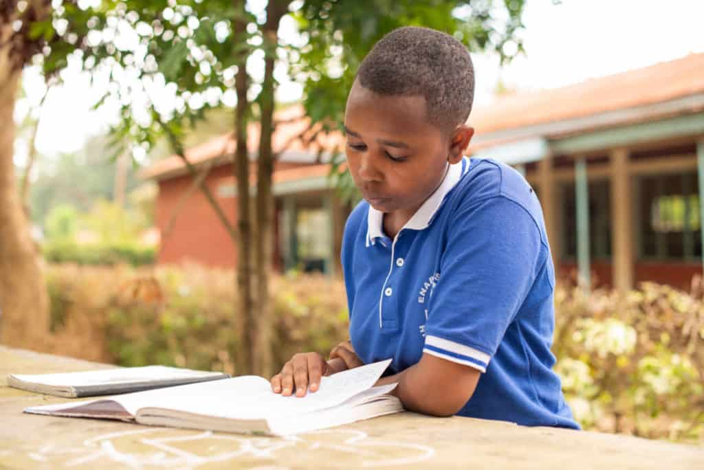 Lilian is wearing a blue polo shirt. She is sitting at a table outside her school and is reading a book.
