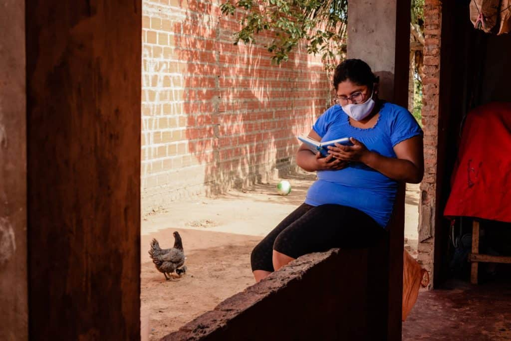 Ana is wearing a blue shirt, black shorts, and a whtie face mask. She is sitting outside her home and is reading a book. There is a chicken in the background.