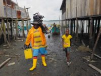 A man carries a bucket and a boat motor as he walks with a boy in from the water.