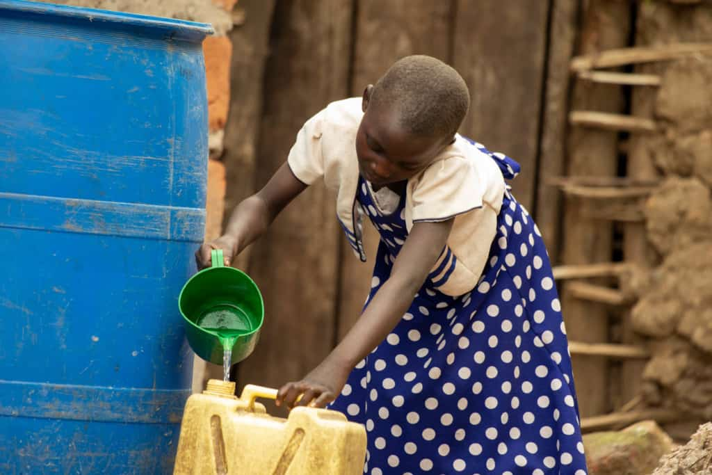Promise is wearing a blue and white polka dotted dress with a white jacket. She is pouring water into a yellow jerry can from a large blue rainwater harvesting tank.