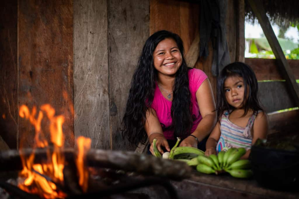 Jaela is wearing a pink shirt. She is in the kitchen of her home with her younger sister, Mayte. They are cooking plantains over an open fire.