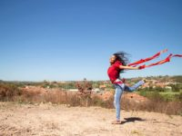 Maria Rita is wearing a red shirt and jeans. She is holding a red ribbon in each hand is jumping in the air. Her town is in the background.